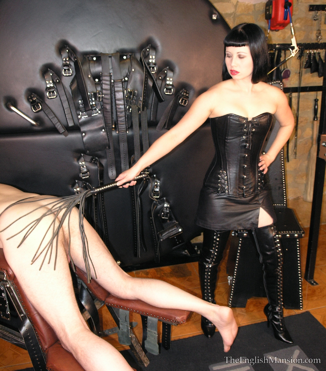 Leather Mistress whips her slave